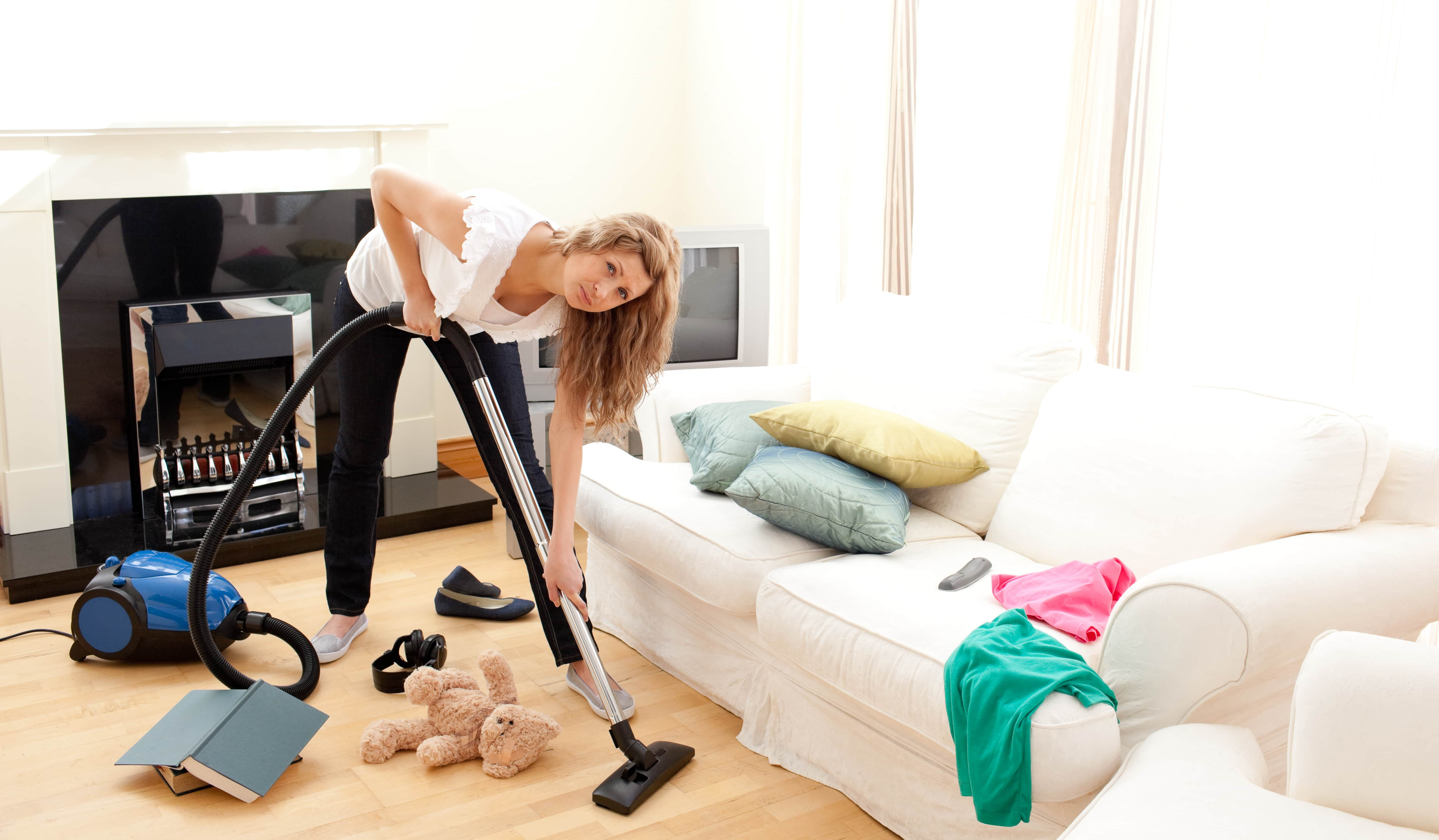 A woman vacuuming the living room with bad posture