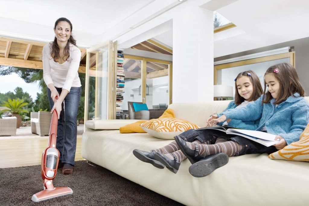 Young mum using a vacuum cleaner while her two twin daughters are on the couch