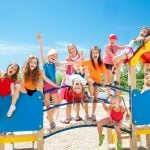 A group of happy children sitting on a playground bridge smiling and posing